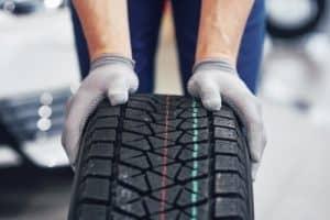Mechanic holding car tyre